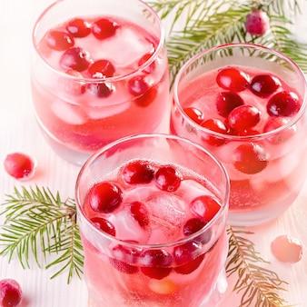 Winter niet-alcoholische cocktail met cranberry en ijs op houten achtergrond, close-up, bovenaanzicht