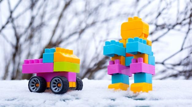 Winter nieuwjaar kinderen speelgoedauto en robot. speelgoed in de sneeuw op straat. cristmas presenteert