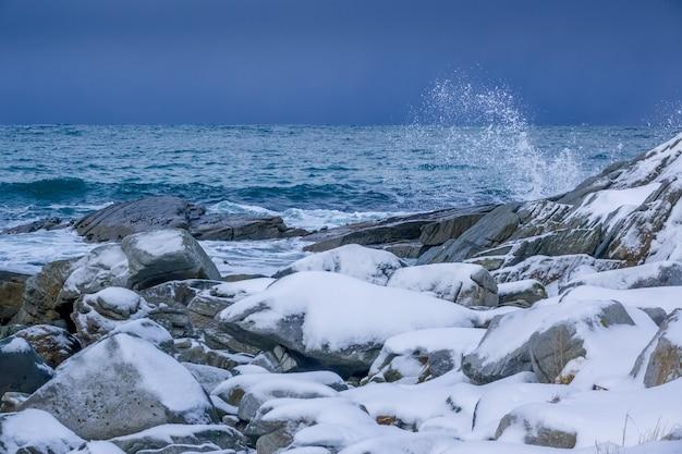 Winter noorwegen. besneeuwde rotsachtige kust van de oceaan. waternevel van de surfgolf