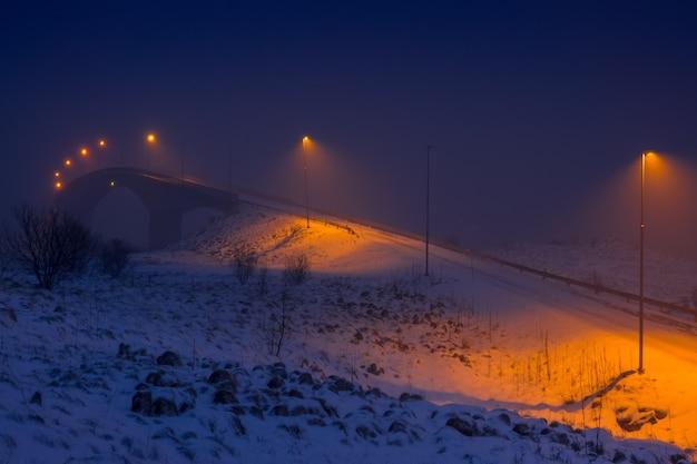 Winter noorwegen. brug met lantaarns over de fjord in de avond en sneeuwval