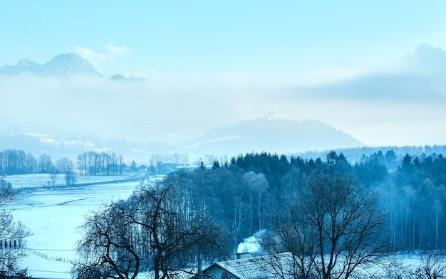 Winter ochtend bergdorp wazig landschap met laaghangende wolken en kasteel in het verre oostenrijk.