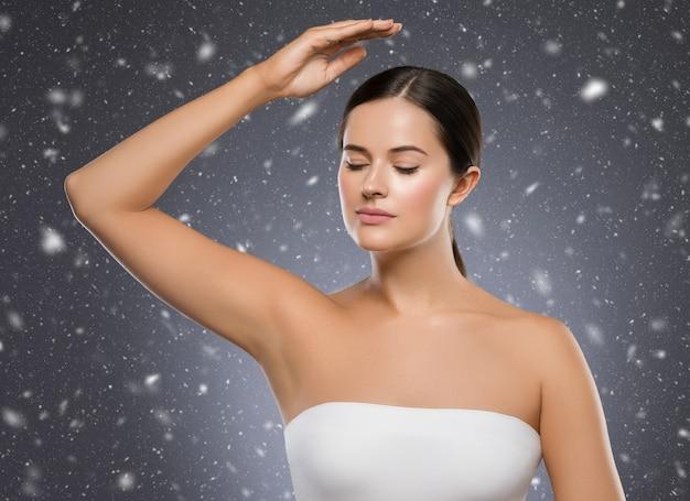 Winter oksel vrouw winter concept sneeuwvlokken achtergrond vrouw hand omhoog schoonheid ontharing. studio opname.
