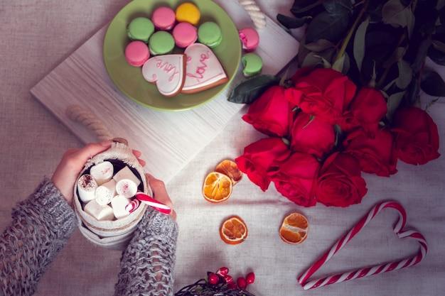 Winter ontbijt op bed met rode rozen en hart van gestreepte lolly