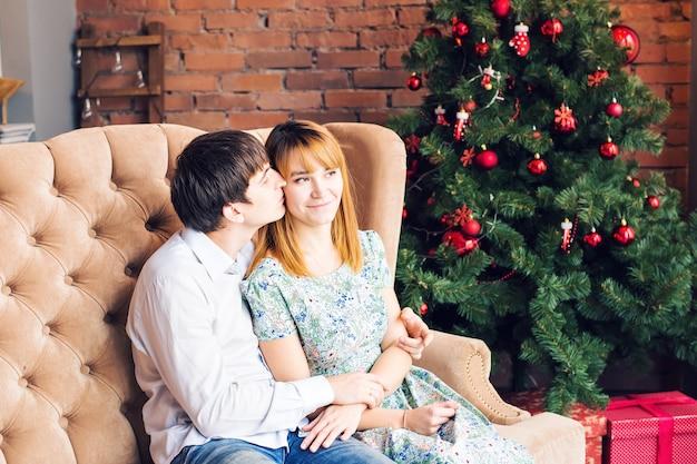 Winter, paar, kerstmis en mensenconcept - glimlachende man en vrouw die over x-mas tree knuffelen