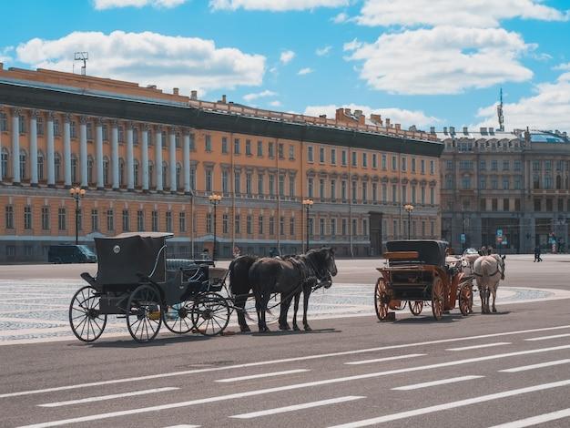 Winter palace plein met vervoer en paarden in sint-petersburg. rusland