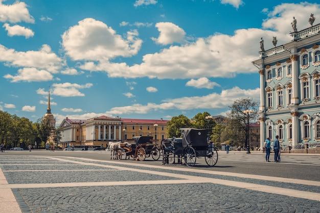 Winter palace plein met vervoer en paarden in sint-petersburg