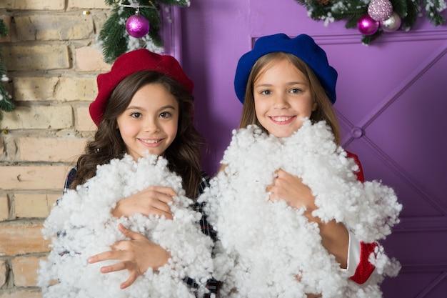 Winter plezier. kleine kinderen met kunstmatige sneeuw. kleine meisjes met kerstversiering. gelukkige kinderen vieren kerstmis en nieuwjaar. kinderspelletjes op wintervakantie. de winter is koel.