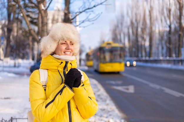 Winter portret van een gelukkige vrouw in een warme gele jas en siberische russische hoed te wachten op een bus op een besneeuwde straat in de stad