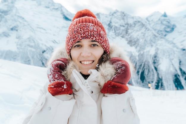 Winter portret van een jonge vrouw in een wit jasje, muts en wanten tegen de achtergrond van bergen. het meisje in de sneeuw.