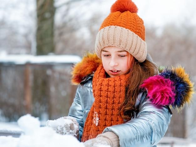 Winter portret van jong meisje. tienermeisje in een hoed bij sneeuwweer.