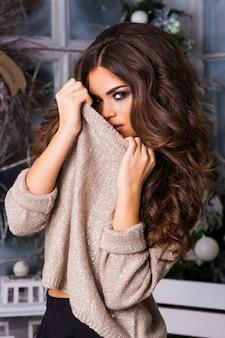 Winter portret van jonge charmante mooie brunette vrouw, gekleed in warme trui bedekt met sneeuw