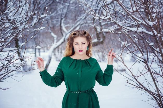 Winter portret van jonge mooie brunette vrouw, gekleed in gebreide haarband bedekt met sneeuw. sneeuwende winter
