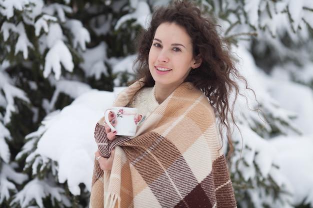 Winter portret van jonge mooie brunette vrouw, gekleed in gebreide haarband bedekt met sneeuw