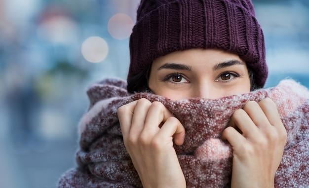 Winter portret van jonge mooie vrouw die betrekking hebben op gezicht met wollen sjaal
