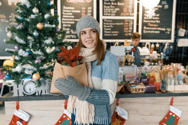 Winter portret van jonge mooie vrouw in gebreide sjaal, gebreide muts, wanten, warme trui met kerst rode poinsettia bloem.