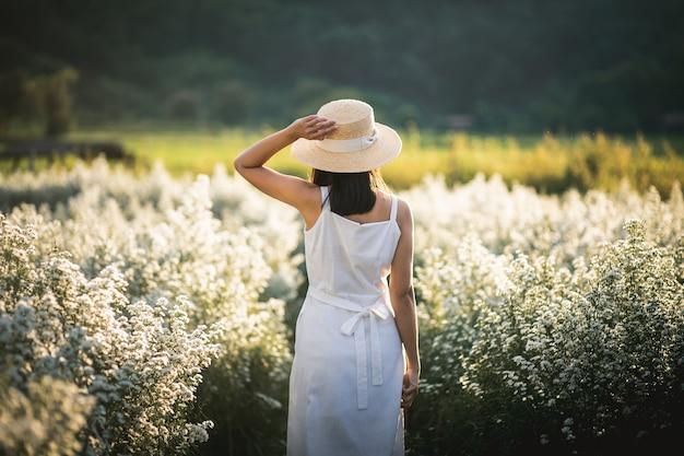 Winter reizen ontspannen vakantie concept, jonge gelukkige reiziger aziatische vrouw met jurk sightseeing op bloemen veld in de tuin in chiang mai, thailand
