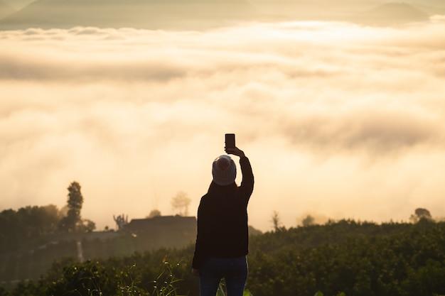 Winter reizen ontspannen vakantie concept, jonge reiziger aziatische vrouw met trui en wollen hoed nemen foto en selfie met mobiele telefoon op berg met mist bij zonsopgang in mae hong son, thailand