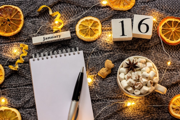 Winter samenstelling. houten kalender 16 januari kopje cacao met marshmallow, lege open kladblok met pen, gedroogde sinaasappels, lichte garland op grijze gebreide achtergrond. bovenaanzicht plat lag mockup