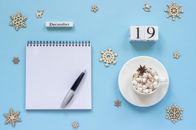 Winter samenstelling. houten kalender 19 december kopje cacao met marshmallow en steranijs, lege open blocnote op lay mockup concept