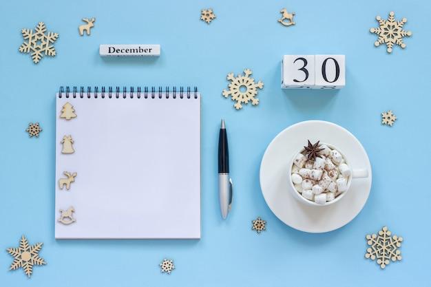 Winter samenstelling. houten kalender 30 december kopje cacao met marshmallow en steranijs, lege open blocnote