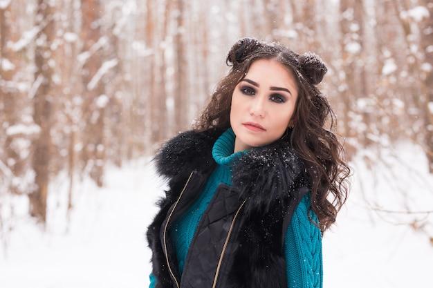 Winter, seizoen en mensen concept - jonge mooie vrouw wandelen in besneeuwde park
