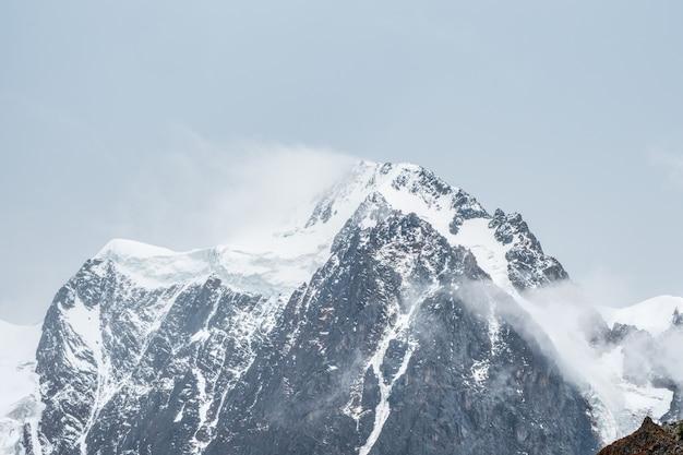 Winter sfeervol berglandschap met sneeuwstorm in grote besneeuwde bergtop in lage wolken. geweldig minimaal landschap met witte gletsjer op zwarte rotsen. hoge bergtop met sneeuw in de wolken.
