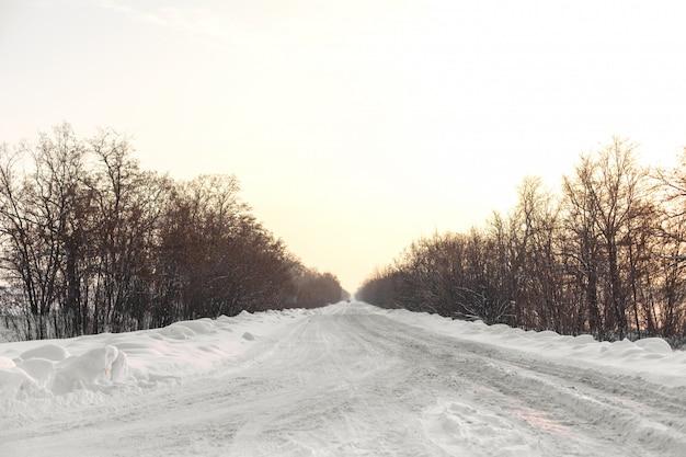 Winter slecht geruimde weg. weg op het platteland dat met sneeuw wordt uitgestrooid. winterlandschap met sneeuwbanken