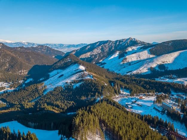 Winter slowakije. blauwe lucht. zonnige dag in het skigebied jasna. bergtoppen en skipistes. luchtfoto