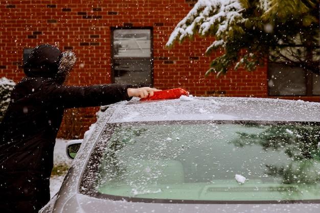 Winter sneeuwstorm vrouw verwijderen na sneeuw uit voorruit met auto sneeuw schoonmaken