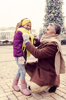 Winter stad. knappe mannelijke persoon die een glimlach op zijn gezicht houdt terwijl hij met zijn dochter praat