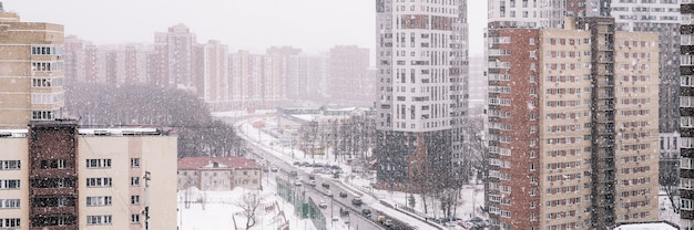 Winter stadslandschap met vallende sneeuw. uitzicht op de stad vanaf een hoogte. sneeuwstorm op straat met sneeuwvlokken. woongebouwen en een weg met rijdende auto's. banier