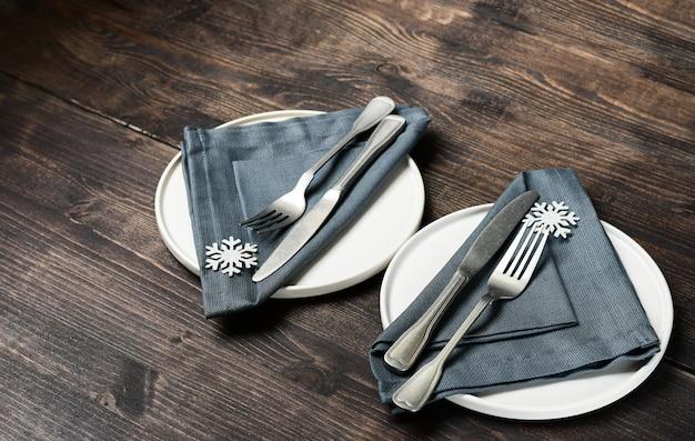 Winter tabel instelling kerst diner lunch. witte ambachtelijke plaat, bestek servet sneeuwvlok decor op een houten tafel