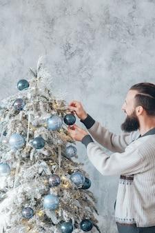 Winter vakantie concept. bebaarde hipster man fir tree versieren met blauwe bal ornamenten.