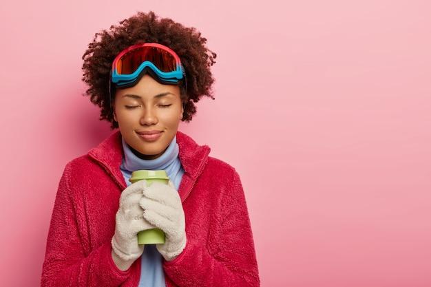 Winter vakantie concept. mooie ontspannen vrouw heeft koffiepauze, warmt zichzelf op met warme drank, draagt snowboardmasker, witte zachte wanten en rode jas, sluit de ogen van plezier