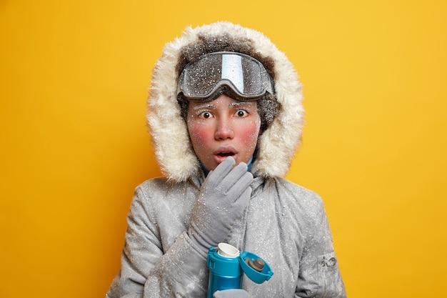 Winter vakantie concept. verrast etnische actieve vrouw geniet van sportactiviteit houdt de mond geopend van shock drinkt warme drank gekleed in bovenkleding.