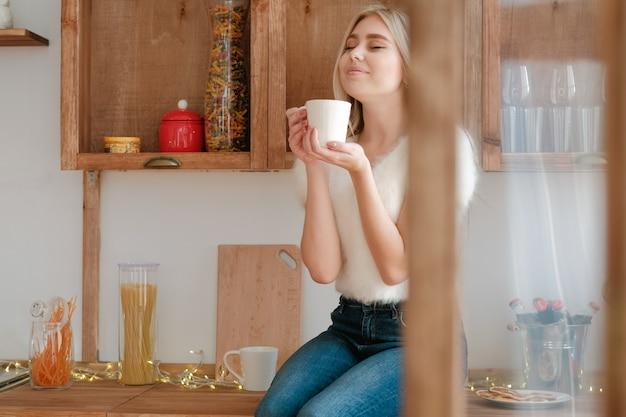 Winter vakantie ochtend. gelukkige dame zittend in de moderne keuken, genieten van warme dranken.
