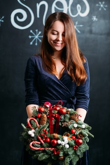 Winter vakantie vieren. mooie dame in blauwe jurk staande met kerstkrans over donkere muur met sneeuw belettering.