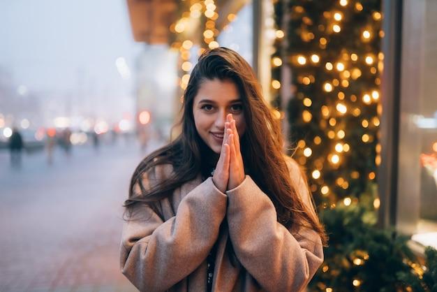 Winter vakantieseizoen. kerstmis, nieuwjaar concept. vrouw door verlichte showcase op straat in de stad.