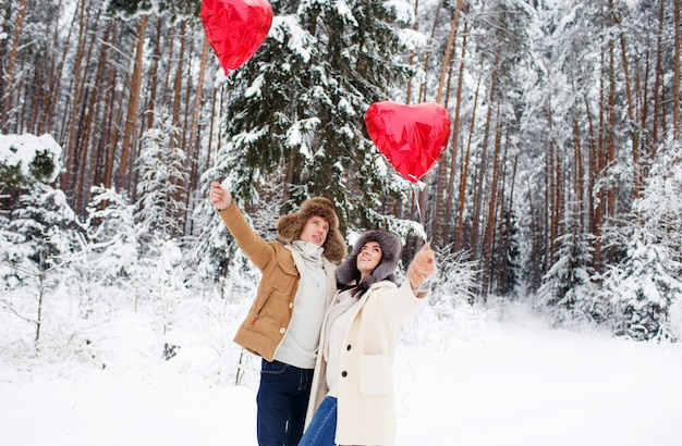 Winter verliefde paar. jongen en meisje knuffelen in de winter sneeuw en het sprookjesbos met ballonnen.