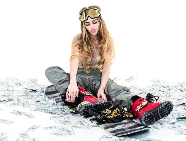 Winter vrije tijd extreme sport snowboard meisje aantrekkelijke atletische vrouw in ski-masker zitten op snowboard