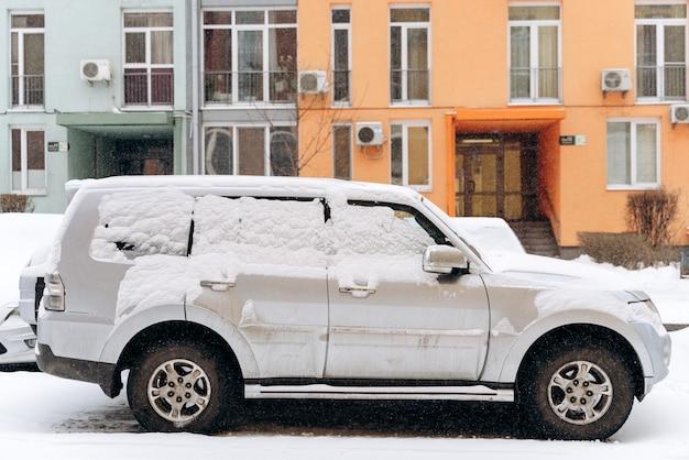 Winter weg in de ochtend. volledige lengte weergave van de grote geparkeerde auto bedekt met sneeuw op straat. sneeuwstorm concept. stock foto