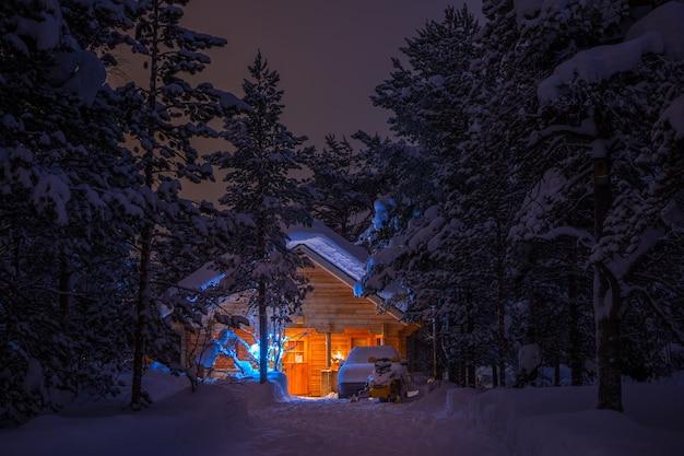 Winter windstille nacht. dicht sparrenbos. houten huis verlicht en veel sneeuw. auto en sneeuwscooter zijn er