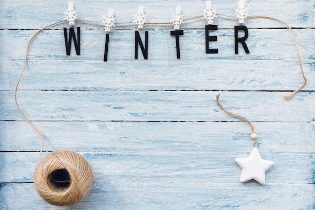 Winter woord vastgemaakt op een touw op blauwe en witte houten achtergrond