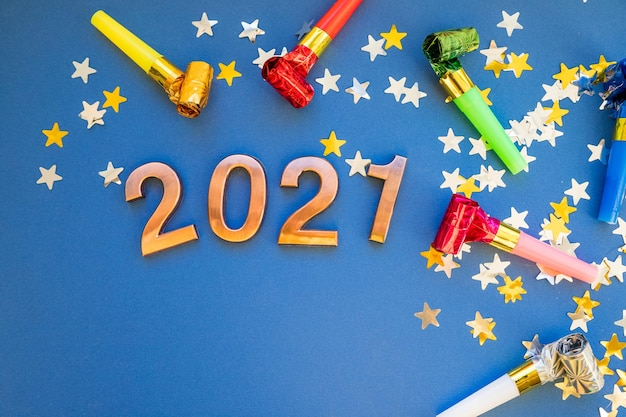 Winter xmas vakantie thema. nummers 2021 met kleurrijke glanzende confetti op blauwe achtergrond. gelukkig nieuw