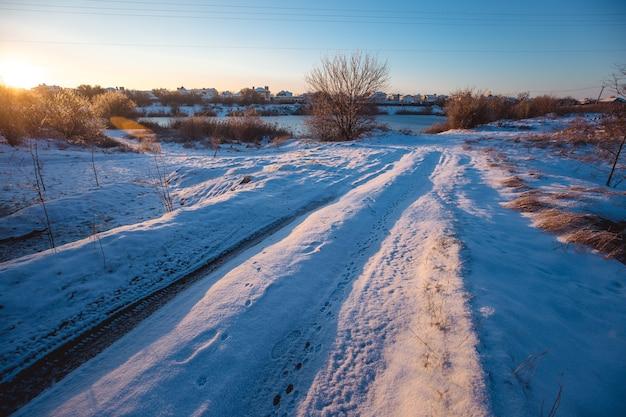Winter zonnige ochtend landschap met een landweg.