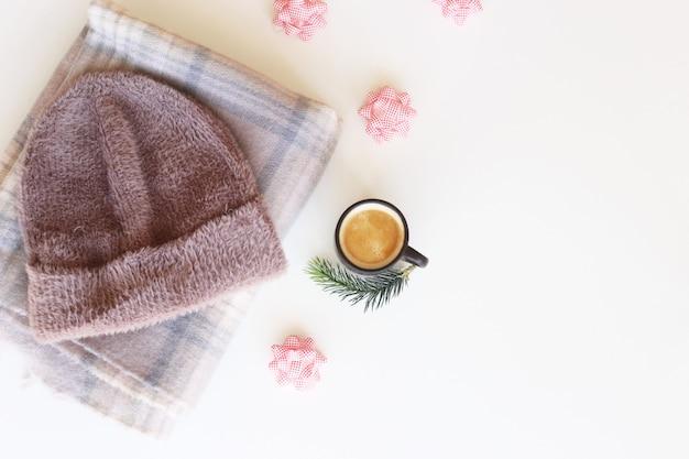 Winteraccessoires voor dames - muts en sjaal naast een kopje koffie en strikken