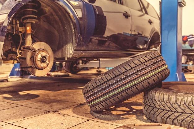 Winterbanden vervangen op zomerbanden in een professionele garage met behulp van professioneel gereedschap. auto op een hydraulische krik