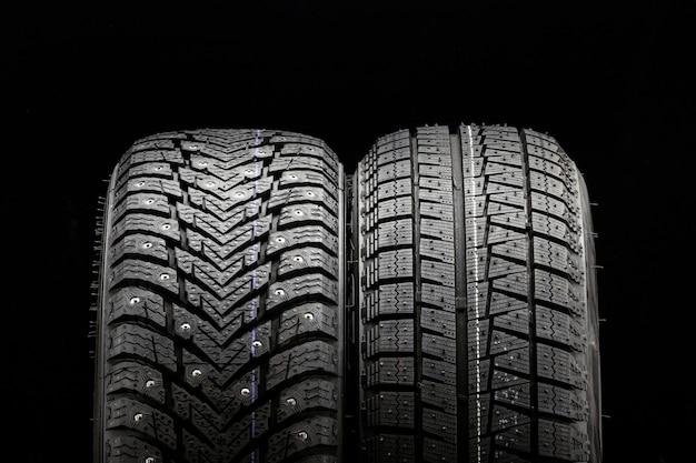 Winterbanden wielen zijn nieuwe zwarte achtergrond. wrijving velcro wiel en spijkerband naast twee stukken.