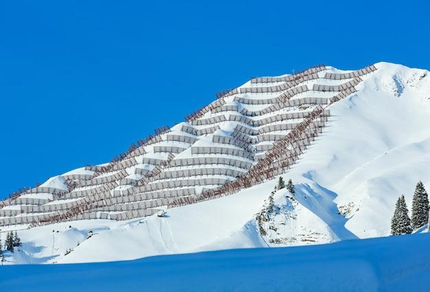 Winterberg met besneeuwde spar en metalen sneeuwbarrière op helling.