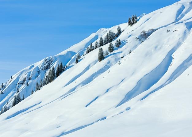 Winterbergheuvel met sneeuwbanken en besneeuwde spar op helling (oostenrijk, tirol).